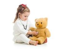 哄骗有使用与玩具的医生衣裳的女孩 库存图片