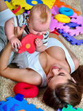 哄骗有使用难题玩具的母亲的男婴  免版税库存照片