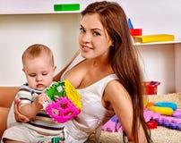 哄骗有使用难题玩具的母亲的男婴  库存图片