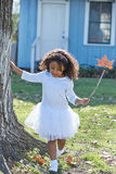 哄骗有室外秋天叶子不可思议的鞭子的女孩 免版税库存图片