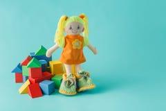 哄骗有木积木的玩偶在简单的背景 库存照片