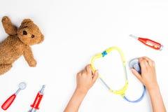 哄骗有玩具听诊器、玩具熊和玩具医学工具的手在白色背景 顶视图 图库摄影