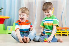 哄骗有玩具的男孩在游戏室 库存照片
