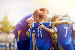 哄骗有的体育队与教练的鼓励性讲话 儿童教练员刺激的足球队员 教练橄榄球青年队 免版税库存照片