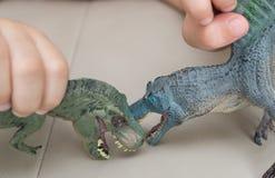 哄骗演奏在沙发的暴龙和spinosaurus玩具 免版税库存照片