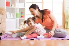 哄骗瑜伽女老师训练孩子 库存照片