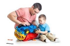 哄骗男孩和他的爸爸定象玩具树干 免版税图库摄影
