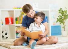 哄骗男孩,并且他的父亲在地板在家读了一本书 免版税库存照片