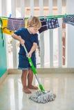 哄骗男孩洁净室,与拖把的洗涤物地板 一点家庭帮手 蒙台梭利概念 免版税库存照片