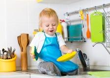 哄骗男孩洗涤的盘和有乐趣在 免版税库存照片