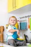 哄骗男孩洗涤的盘和有乐趣在 免版税库存图片