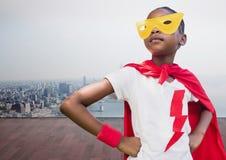 哄骗站立用在臀部的手的佩带的红色海角和黄色面具反对都市风景背景 库存图片