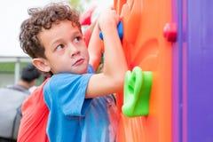 哄骗获得的男孩乐趣使用在儿童` s上升的玩具在学校 库存图片