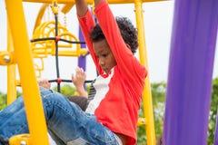 哄骗获得的男孩乐趣使用在儿童` s上升的玩具在学校 免版税库存照片