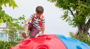 哄骗获得的男孩和的背包乐趣使用在攀登t的儿童` s 库存照片