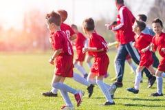 哄骗足球橄榄球-行使在比赛前的儿童球员 免版税库存图片