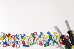 哄骗建筑在白色背景的工具框架 五颜六色的玩具塑料螺栓、坚果和螺丝刀在线安排了 免版税库存图片