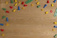 哄骗建筑玩具工具边界 五颜六色的螺丝和坚果在木背景 顶视图 平的位置 免版税库存照片
