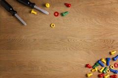 哄骗建筑玩具工具:五颜六色的螺丝刀、螺丝和坚果在木背景 顶视图 复制文本的空间 库存图片