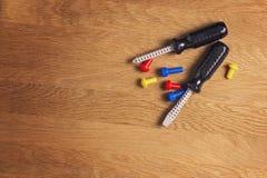 哄骗建筑玩具工具:五颜六色的螺丝刀、螺丝和坚果在木背景 顶视图 平的位置 复制 免版税图库摄影