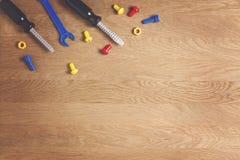 哄骗建筑玩具工具:五颜六色的螺丝刀、螺丝和坚果在木背景 顶视图 平的位置 复制 免版税库存照片