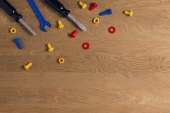 哄骗建筑玩具工具:五颜六色的螺丝刀、螺丝和坚果在木背景 顶视图 平的位置 复制 库存照片