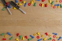 哄骗建筑玩具工具:五颜六色的螺丝刀、螺丝和坚果在木背景 顶视图 平的位置 复制 图库摄影