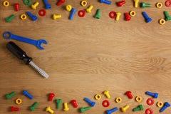 哄骗建筑玩具工具:五颜六色的螺丝刀、螺丝和坚果在木背景 顶视图 平的位置 复制 库存图片