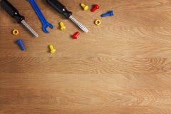 哄骗建筑玩具工具:五颜六色的螺丝刀、螺丝和坚果在木背景 顶视图 平的位置 免版税图库摄影