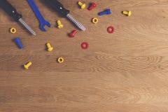 哄骗建筑玩具工具:五颜六色的螺丝刀、螺丝和坚果在木背景 顶视图 平的位置 免版税库存图片