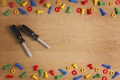 哄骗建筑玩具工具:螺丝刀、螺丝和坚果在木背景 顶视图 平的位置 免版税图库摄影