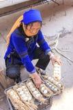 哈妮妇女在盛村地方市场上的卖鸡蛋在原阳 哈妮是56少数之一在中国并且是Yua的当地人 免版税库存图片