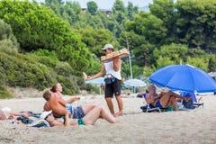哈尔基季基州,中马其顿,希腊 甜酥皮点心的卖主为沙滩的松弛游人提供他的物品 图库摄影