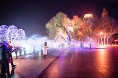 哈尔滨冰节日,人们在斯大林在晚上停放获得与闪烁发光物的乐趣,没有面孔 图库摄影