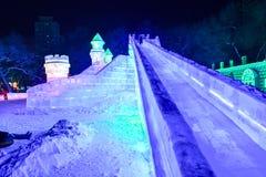 哈尔滨冰节日2018长的幻灯片-意想不到的冰和雪大厦,乐趣, sledging,夜,旅行瓷 库存图片