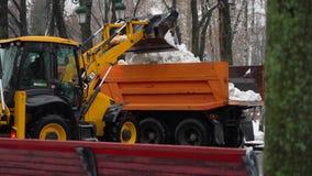 哈尔科夫,乌克兰- 2018年12月22日:挖掘机装载的雪到卡车里在城市公园 股票录像