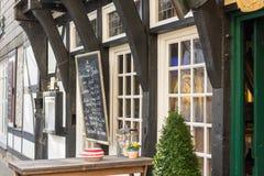 哈廷根,德国- 2017年2月15日:一家餐馆在一个历史的半木料半灰泥的房子吸引有书面的菜单的顾客  库存照片