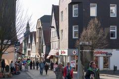 哈廷根,德国- 2017年2月15日:Unidenfied顾客沿主要购物街道走并且享用温暖的太阳 免版税库存照片
