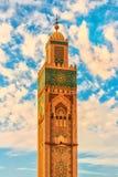 哈桑二世在海滩的清真寺塔日落的卡萨布兰卡,摩洛哥 库存照片