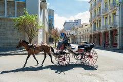 哈瓦那,古巴- 2017年10月20日:五颜六色的哈瓦那老镇建筑学和骑乘马在街道上 库存图片