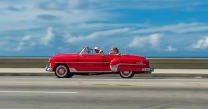 哈瓦那,古巴- 2017年10月20日:移动的老汽车在Malecon,哈瓦那 古巴 与游人的观光旅游 免版税图库摄影