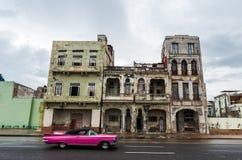 哈瓦那,古巴- 2017年10月21日:老大厦在哈瓦那,独特的古巴建筑学 在前景的移动的汽车 免版税库存图片
