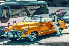 哈瓦那,古巴- 9月 2017年:老20世纪50年代桔子,在背景的旅游公共汽车葡萄酒减速火箭的美国汽车  免版税库存照片