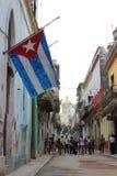 哈瓦那,古巴- 11月20日2015年:有被破坏的大厦和一面非常大古巴旗子的哈瓦那旧城的典型的街道 免版税库存照片
