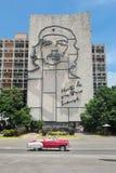 哈瓦那,古巴, 2016年8月16日:葡萄酒汽车在偶象切・格瓦拉` s壁画前面驾驶在革命正方形 免版税库存图片