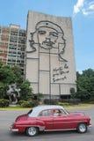 哈瓦那,古巴, 2016年8月16日:葡萄酒汽车在偶象切・格瓦拉` s壁画前面驾驶在革命正方形 库存图片