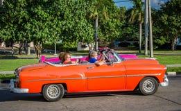 哈瓦那, CUBA-OCT 25 -游人聘用作为出租汽车使用的古董车在哈瓦那, 2015年10月25日 库存照片