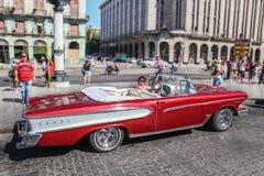 哈瓦那/古巴- 07/2018:在哈瓦那租赁的五十年代老和生锈的汽车  从旁边proection的红色Edsel步测器与白种人woma 库存照片