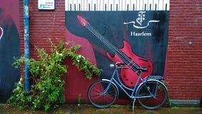 哈莱姆舒适庭院:在墙壁上的美好的街道画有一把吉他和题字的与城市和自行车的名字 库存照片