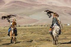 哈萨克人与马的老鹰猎人Berkutchi教他的女儿对寻找对与的野兔鹫 免版税图库摄影